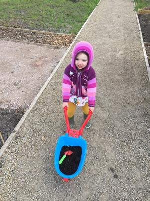 child helping dad move soil to reach his goal and plans for the allotment